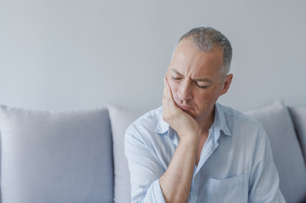 Toothache. Frustrated young man touching his cheek and keeping eyes closed while sitting on the couch at home. Toothache, medicine, health care concept, Teeth Problem