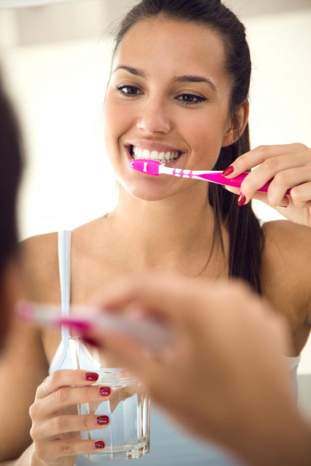 bastante-jovem-escovando-os-dentes-no-banheiro_1301-7647